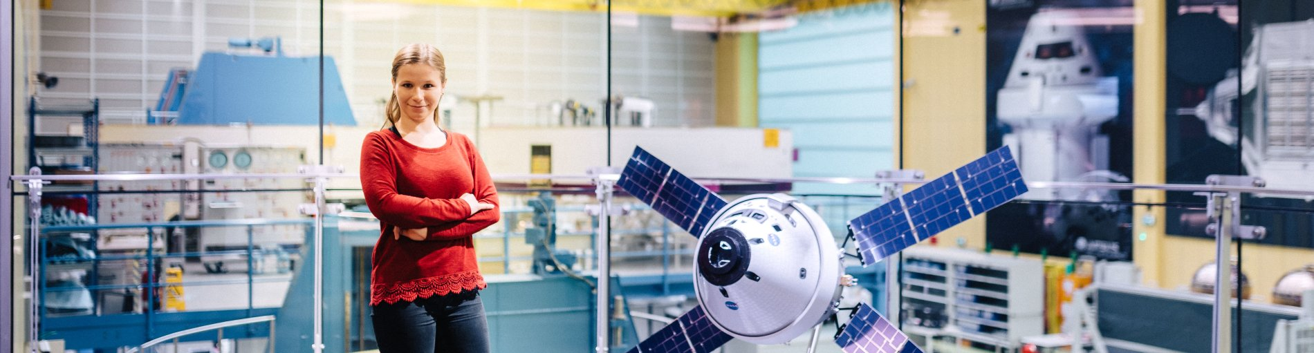 Eine Frau in rotem Pullover steht in einem Labor.