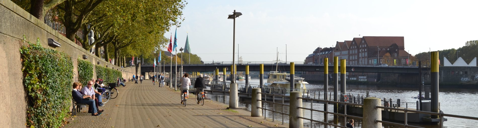 Eine Promenade mit Menschen am Fluss, im Hintergrund eine Brücke, die über den Fluss führt.
