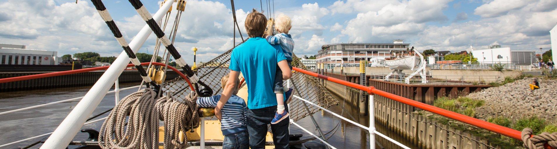 Ein Mann steht mit seinen zwei Kindern am Bug der Schulschiff Deutschland