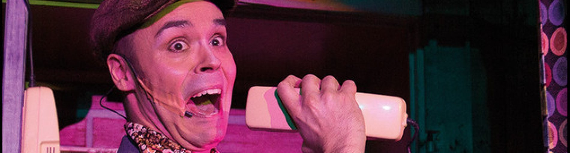 Ein Darsteller des Hafenkrimis mit einem Telefon auf der Bühne.