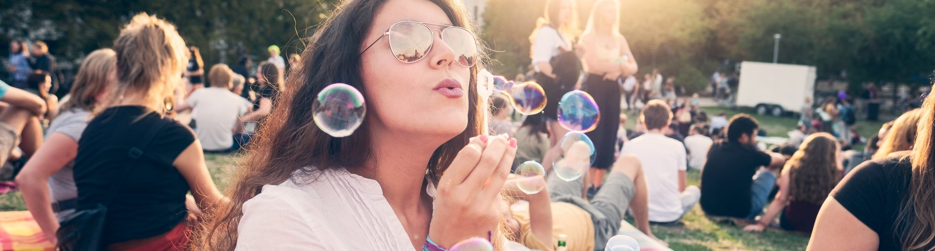 Viele junge Leute stehen im Sommer auf der Festivalwiese. Im Vordergrund macht eine junge Frau mit Sonnenbrille Seifenblasen.
