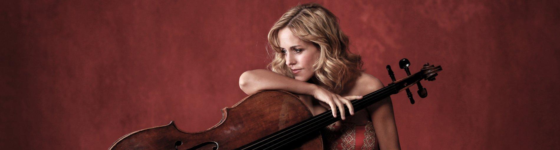 Sol Gabetta sitzend vor einer roten Wand mit ihrem Cello