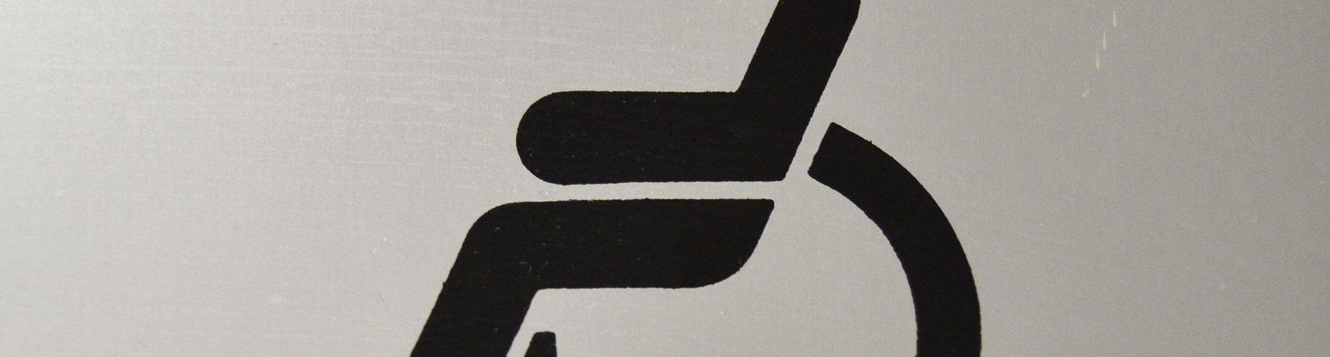 Türschild, symbolische Darstellung einer Person im Rollstuhl