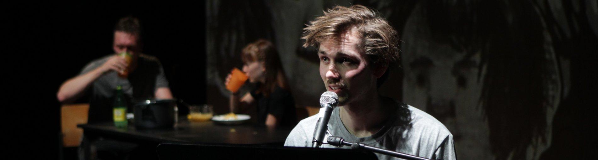Ein Schauspieler sitzt und spricht in ein Mikrofon. Im Hintergrund sind zwei Personen zu sehen, die an einem Tisch sitzen und aus bunten Bechern trinken.