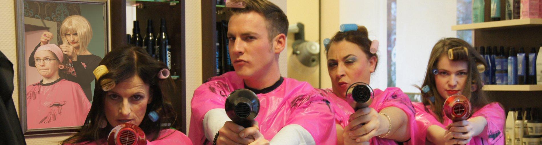 Zu sehen ist ein Szenario im Frisörsalon mit Personen in rosafarbenen Umhängen und einem Föhn in der Hand.
