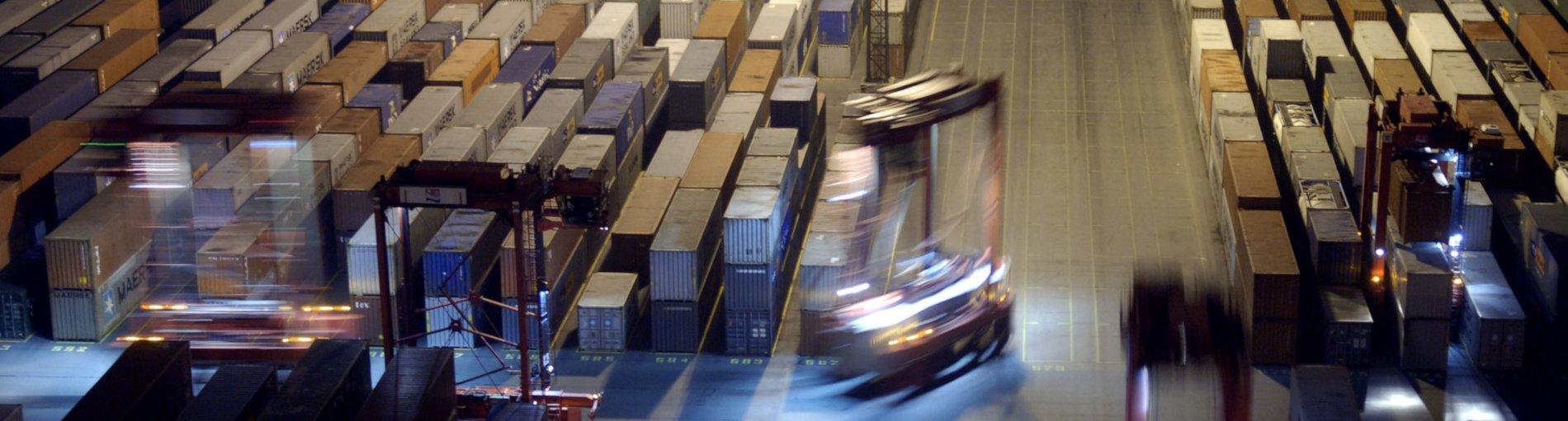 Fahrender Stapler im Containerterminal bei Nacht