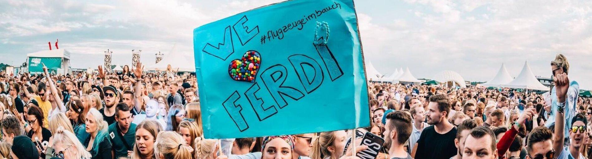 Ein Mädchen hält in der Konzertmenge ein buntes Plakat hoch.