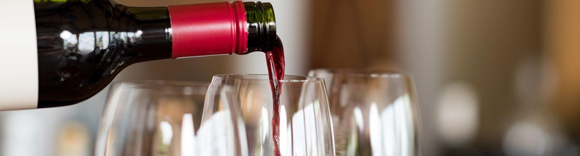 Drei gefüllte Weingläser, eine Flasche gießt Rotwein in eines der Gläser.