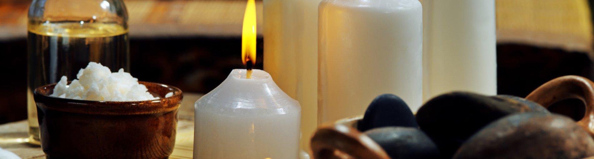 Im Vordergrund brennende Kerzen, Öle und Steine, im Hintergrund eine entspannende Frau mit geschlossenen Augen.