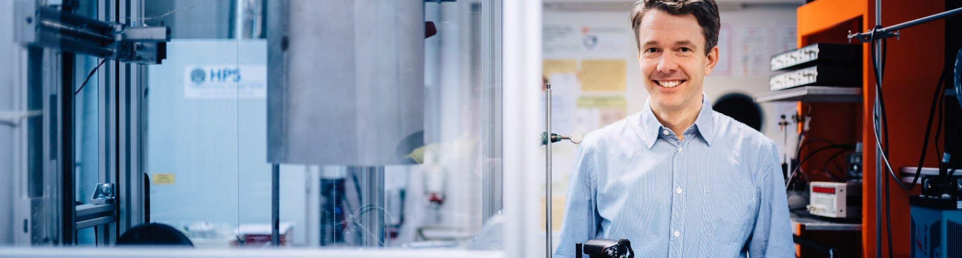 Ein Mann schaut in die Kamera, im Hintergrund ein Forschungslabor; Quelle WFB/Jonas Ginter