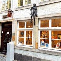 Außenansicht einer Kunstgalerie mit verschiedenen Skulpturen und Malereien hinter erleuchteten Fenstern.