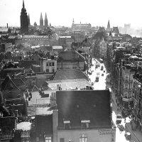 Zu sehen ist die Aussicht von oben auf eine Stadt mit vielen Häusern und spitzen Türmen. Da ist schwarz-weiß. Rechts im Bild befindet sich eine Straße, die von Häusern gesäumt ist und auf der Autos fahren.