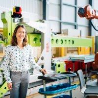 Eine Frau lacht in die Kamera, im Hintergrund stehen Maschinen; Quelle: WFB/Jonas Ginter