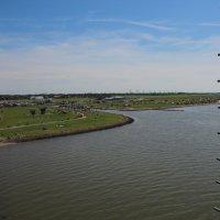 Auf großen, grünen Wiesen, die an das Meer grenzen, befinden sich Menschen, Zelte, Autos und Häuser