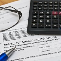 Ein Taschenrechner, eine Brille und ein Kugelschreiber liegen auf einem Ausbildungsförderungsantrag auf einem Holztisch