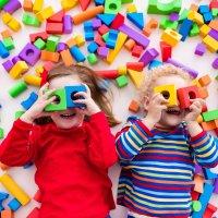 Zwei Kinder halten sich Spielholzklötze vor die Augen und gucken in die Kamera. Um sie herum liegen viele bunte Bauklötze