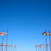 Unterschiedlichste Fahnen aus verschiedenen Ländern wehen im Wind vor blauem Himmel. Sie sind an Maste im Kreis arrangiert.