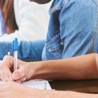Schüler sitzen in einer Reihe an Tischen und schreiben etwas auf; Quelle: fotolia/Robert Kneschke