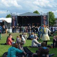 junge Menschen sitzen vor einer Bühne auf dem Festivalgelände