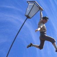 Der Akrobat Noah Chorny an einer Straßenlaterne hängend.