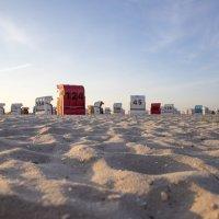 Weißer Sandstrand, an dessen Ende weiße, rote und blaue Strandkörbe von hinten zu sehen sind. Dahinter ist hellblauer Himmel zu erkennen.