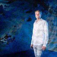 Ein Mann vor einer Nachbildung des Monds.