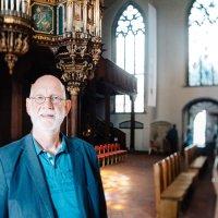 Ein Mann in einer Kirche. Im Hintergrund ist eine Orgel.