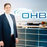 Mann steht vor einem OHB-Logo