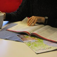 Frauenhand blättert in dem neuen Katalog der VHs und schaut sich das Programm an