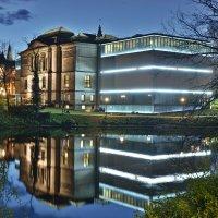 Die beleuchtete Kunsthalle spiegelt sich am Abend in einem See in den Wall-Anlagen
