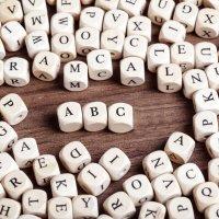 Holzwürfel mit vielen verschiedenen Buchstaben bedruckt, in der Mitte das ABC