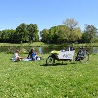 Zwei Frauen und ein Kind machen ein Picknick neben einem Lastenrad.