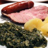 Ein angerichteter Teller mit Grünkohl, Kassler, Kartoffeln und Pinkel.