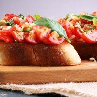 Bruschetta: geröstete Brotscheiben mit Tomate und Basilikum auf einem Holzbrett