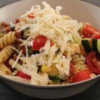 Eine Schale mit buntem Nudelsalat, mit Gemüse und Parmesan-Käse.