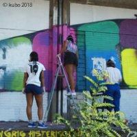 Drei Mädchen sprühen ein Graffiti