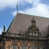Das kupferfarbene Dach des Rathauses vor blauem Himmel