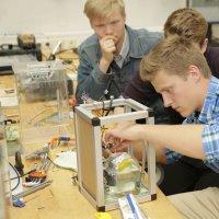 Drei Schüler bauen gemeinsam an einem Modell.