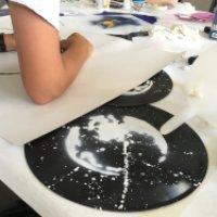 Raumfahrtmotive werden auf Schalplatten gemalt.