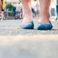 Ein Spaziergang, es sind zwei paar Füße zu sehen und ein Langstock.