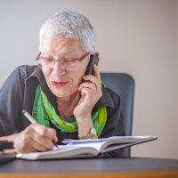 Eine Seniorin schreibt etwas in eine Notizbuch, während sie telefoniert.