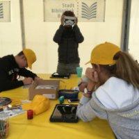 Kinder basteln an einem Tisch während ein Junge in eine VR-Brille aus Pappe reinschaut.
