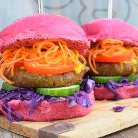 Eine Großaufnahme von einem veganen Burger. Das Brötchen ist rosa.
