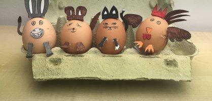 In einem Eierkarton befinden sich vier braune Eier, die jeweils mit Ohren, Pfoten und Gesichtern zu den Bremer Stadtmusikanten verschönert.