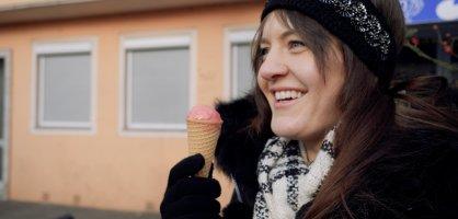 Zu sehen ist eine weibliche Person, die eine Eiswaffel in der Hand hält und lächelt. Die Person trägt ein schwarzes Stirnband, einen weißen schal sowie schwarze Handschuhe.