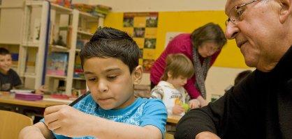 Ein Kind und ein älterer Mann über einer Mathe-Aufgabe; Quelle: Freiwilligen-Agentur Bremen/Susanne Frerichs