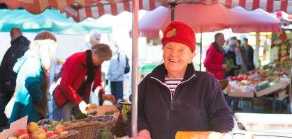 Ein Verkäuferin an einem Marktstand lächelt in Richtung Kamera