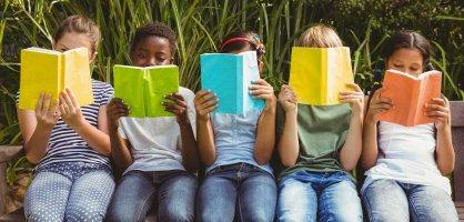 5 Kinder die lesend auf einer Bank im Grünen sitzen