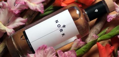 Eine Flasche NORK zwischen Blumen