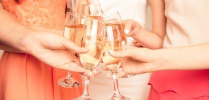 Fünf Frauen stoßen mit einem Glas Sekt an